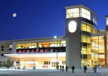 Exterior of a hopsital Emergency Room lit up at night